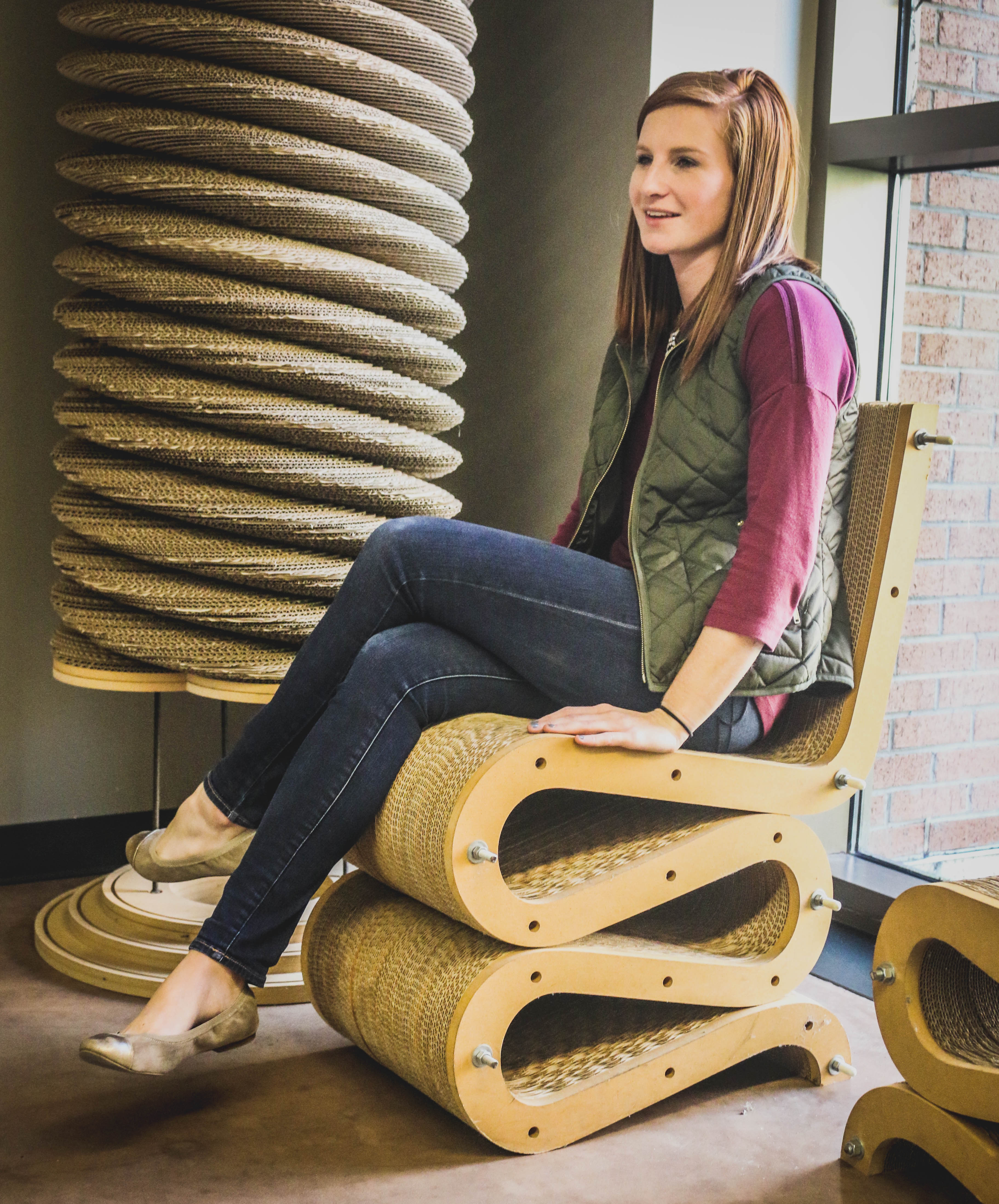Erin Hongsermeier, senior packaging science major, uses a chair made out of layers of corrugated board.